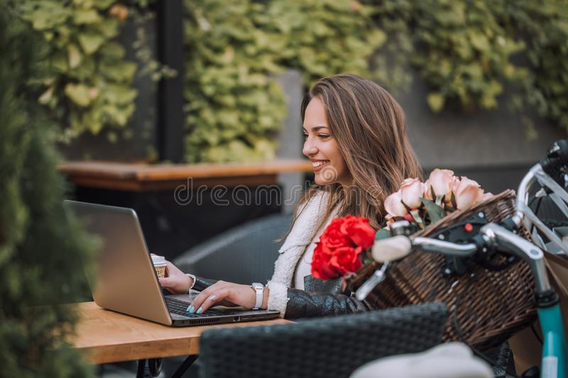 Happy woman using laptop in street cafe royalty free stock images