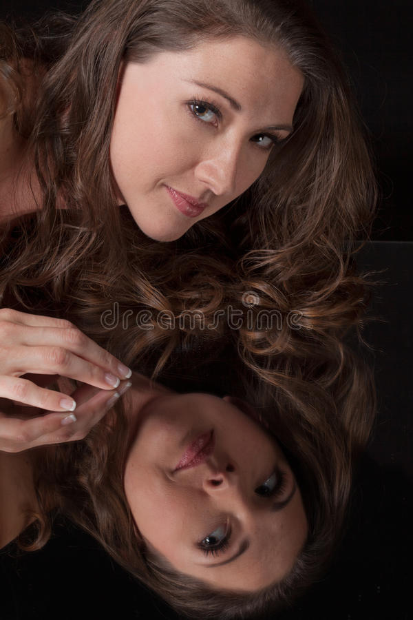 Smiling Woman Leaning Over Mirror royalty free stock images