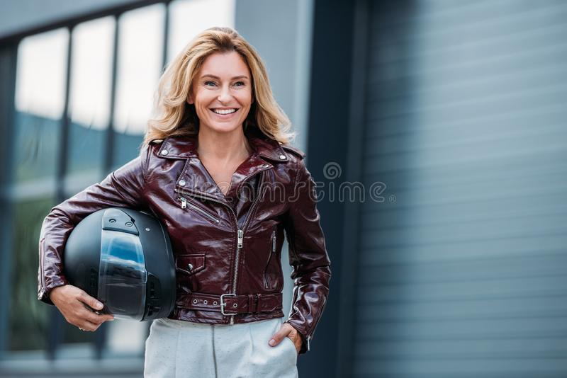 smiling woman in leather jacket holding motorcycle helmet on street royalty free stock image