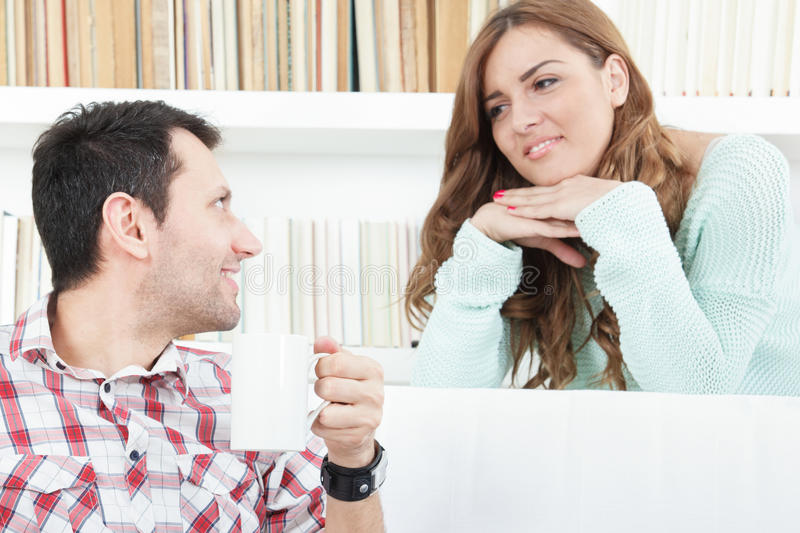 Smiling woman listening carefully to her man. Smiling women listening carefully to her man, couple talking and listening to each other royalty free stock photo