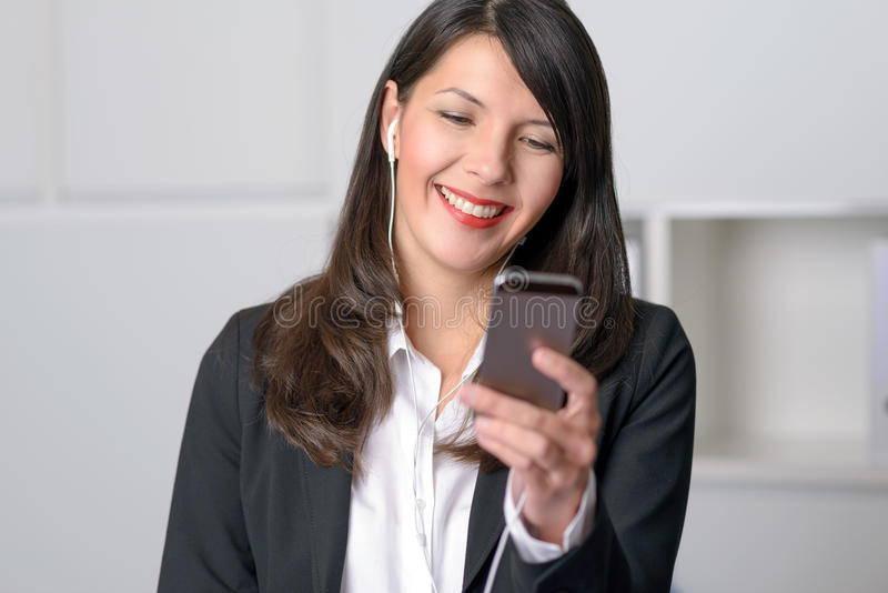 Smiling woman listening to music. Smiling young professional woman listening to music on her MP3 player using earplugs as she happily selects a tune from her royalty free stock photography