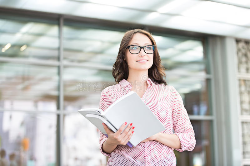 Smiling woman looking away while holding outside building royalty free stock photography