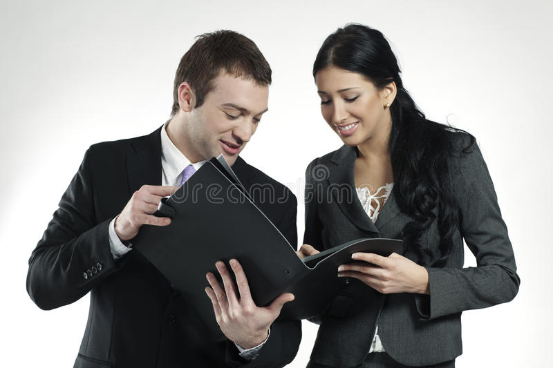 Smiling an and woman looking at business portfolio. Businessman and businesswoman looking at black portfolio stock photos