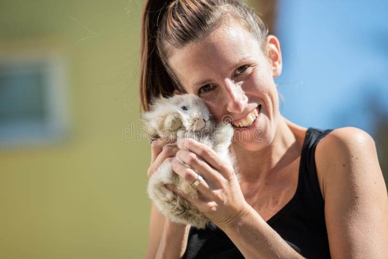Smiling woman looking at camera holding baby rabbit in her hands stock images