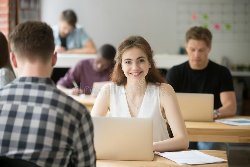Smiling woman looking at camera sitting at desk in co-working stock image