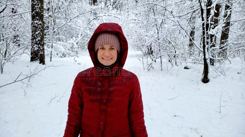 Smiling woman looking at camera in snow covered forest, enjoying winter nature. Stock photo stock photos