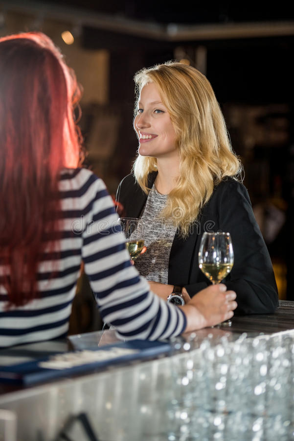 Smiling Woman Looking At Friend In Bar. Smiling young women looking at female friend at bar counter royalty free stock photography