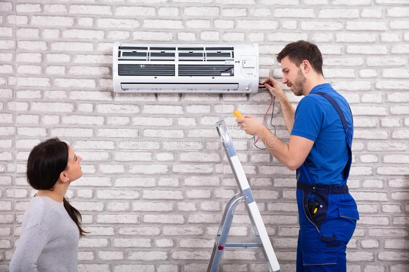 Technician Repairing Air Conditioner With Digital Multimeter. Smiling Woman Looking At Male Technician Repairing Air Conditioner With Digital Multimeter At Home royalty free stock photo