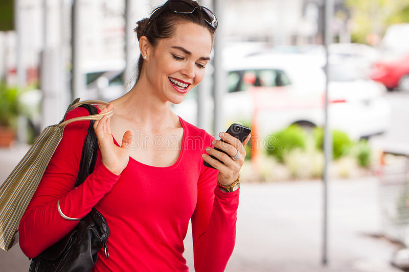Smiling woman looking at mobile phone stock photos