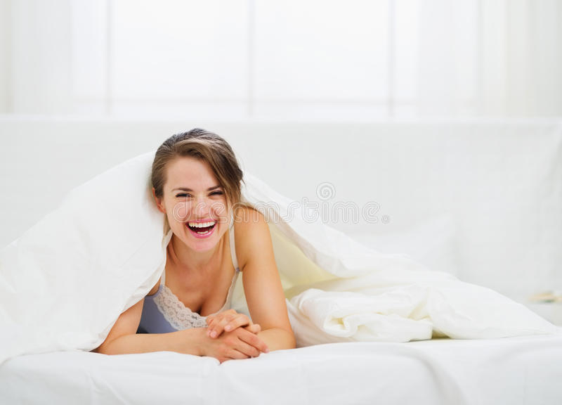 Download Smiling Woman Looking Out From Blanket Stock Image - Image: 25313955