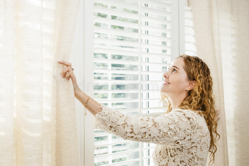 Smiling Woman Looking Out Window Royalty Free Stock Photography