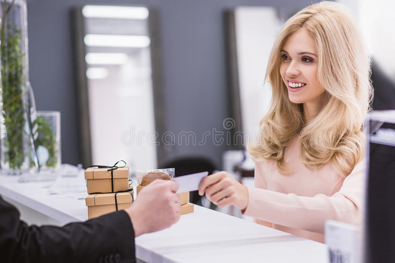 Smiling woman is looking at receptionist stock photography