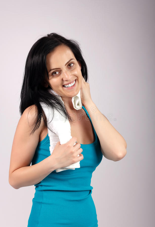 Smiling woman looking to camera and wiping sweat royalty free stock images