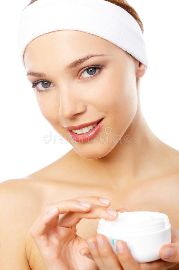 Smiling woman with lovely skin applying cream royalty free stock image