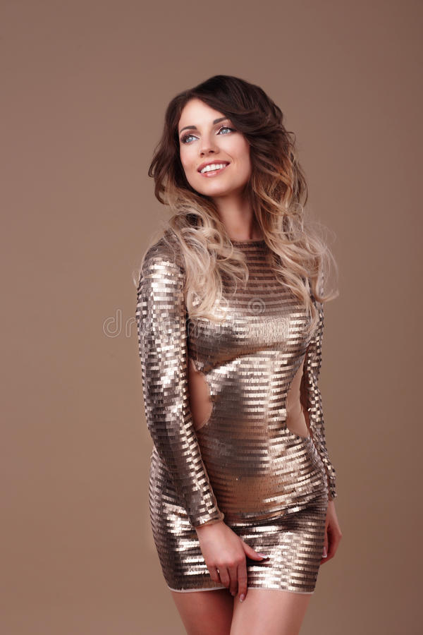 Smiling woman in luxurious glitter dress. royalty free stock images