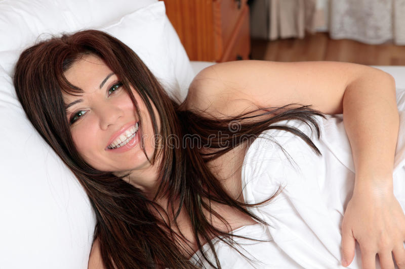 Smiling woman lying in bed stock images