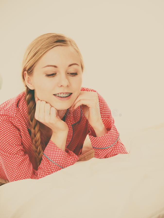 Smiling woman lying in bed royalty free stock photography