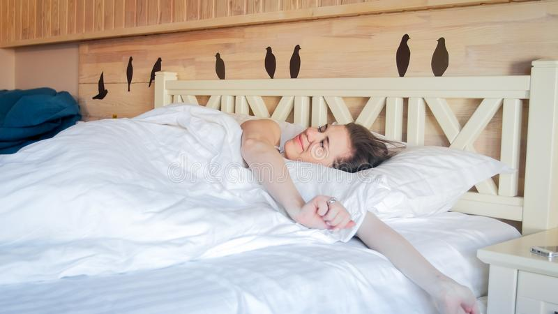 Beautiful smiling woman lying in bed and stretching stock photo