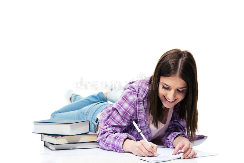 Smiling woman lying on the floor and writing in notebook royalty free stock photo