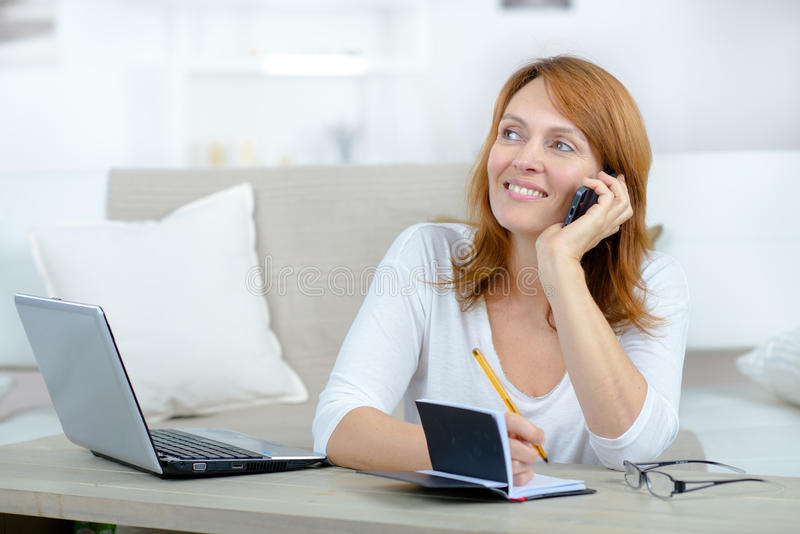 Smiling woman making appointment in diary royalty free stock photography