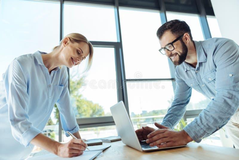 Smiling woman making notes while man using laptop royalty free stock image