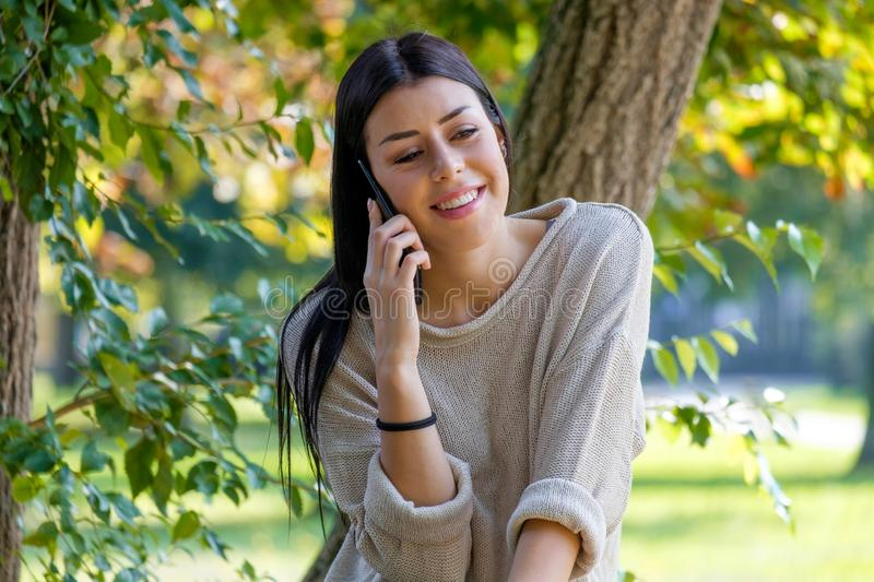Happy young woman making a phone call outdoor stock photos