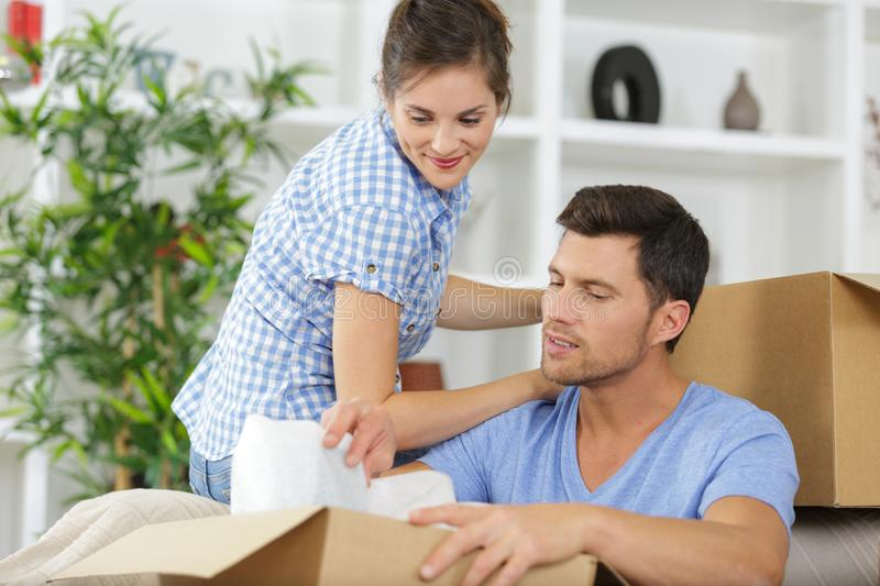 Smiling woman and man packing stuff stock photography
