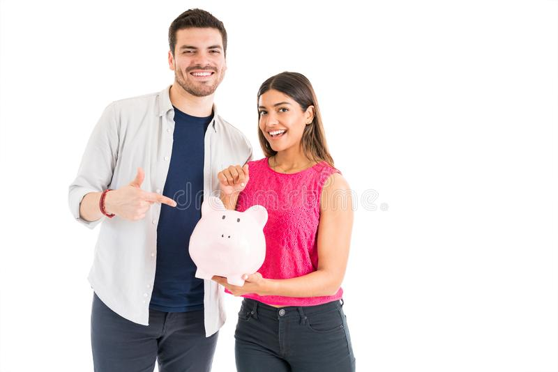 Smiling Woman And Man Pointing At Coin Bank In Studio. Portrait of a good looking young couple holding their savings in a piggy bank against plain background royalty free stock photos