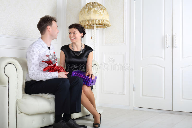 Smiling woman and man sit at white sofa with gifts. Smiling women and men sit at white sofa with gifts in light room stock images