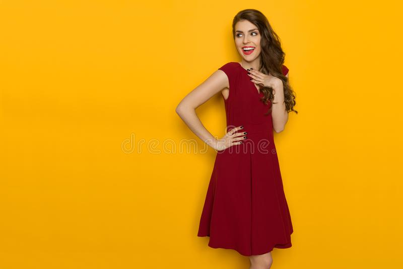 Smiling Woman In Maroon Dress Is Looking Away. Happy beautiful young woman in maroon dress is holding hand on chest, looking away over the sholder and smiling stock photo