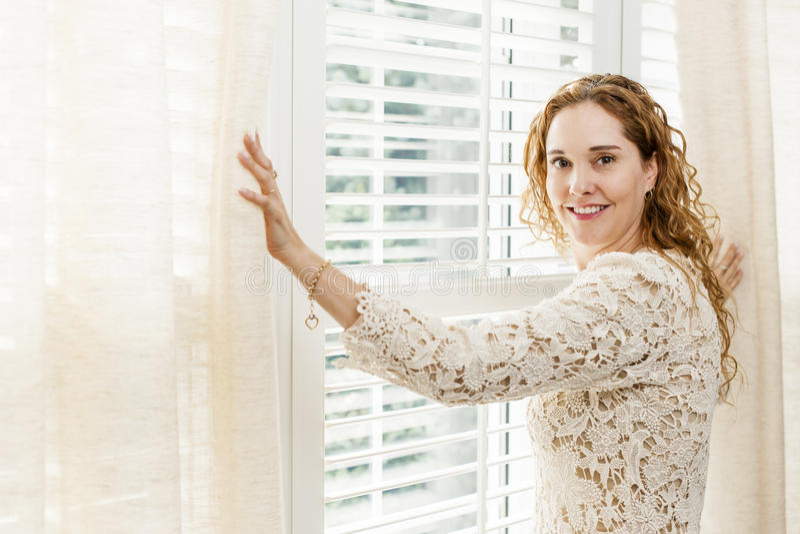 Smiling woman near window royalty free stock photos