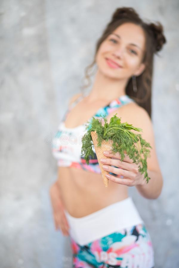 A smiling woman offers a waffle cone with dill and parsley instead of ice cream cone royalty free stock photography