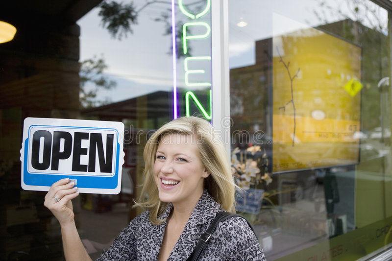 Smiling woman with an open sign. A happy owner holding up an Open sign in front of her new business stock image
