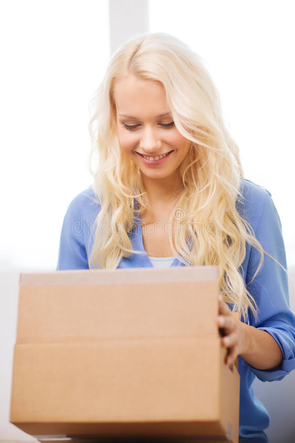 Smiling Woman Opening Cardboard Box At Home Stock Photo ...
