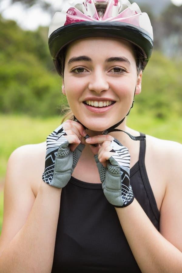Smiling woman opening her helmet stock image