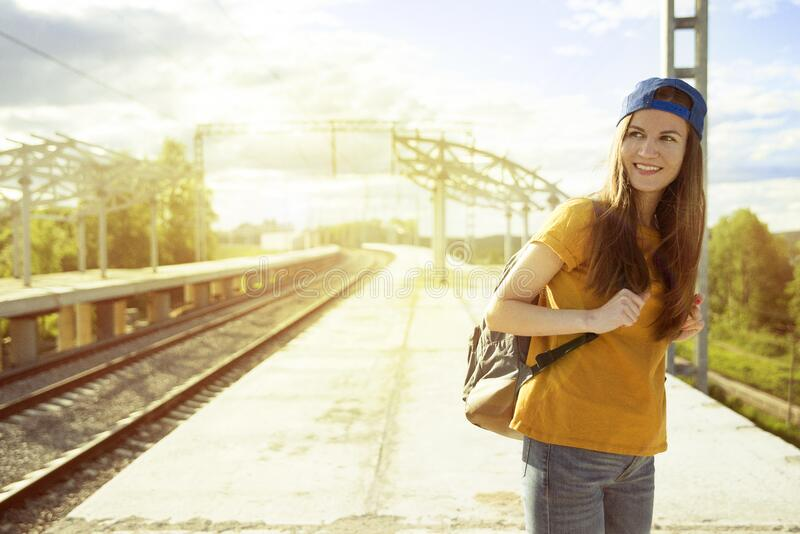 Smiling Woman in Orange T Shirt and Blue Snap Back Cap Carrying Backpack stock image