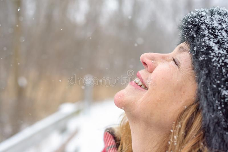 Smiling woman outside looking up letting snow fall on face stock images