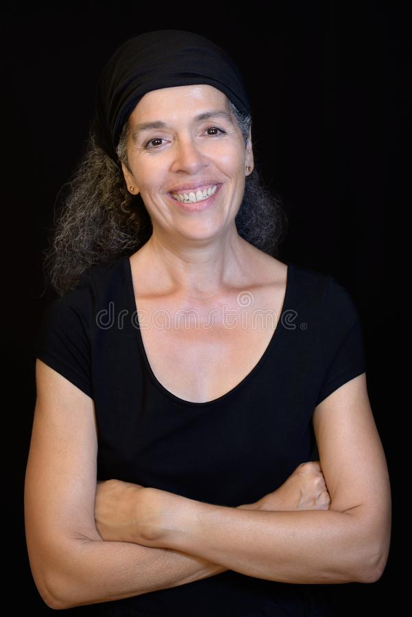 Smiling woman 50+ portrait wearing black Black background. A smiling woman over fifty with graying hair. Black hair band, black t-shirt, black background stock image