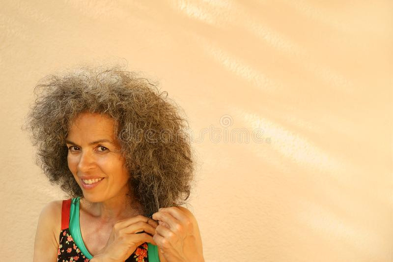 Smiling woman over 50 pulling on her graying hair. A smiling mature woman is pulling on her graying curly hair. Southern type wearing a summer outfit. Apricot royalty free stock images