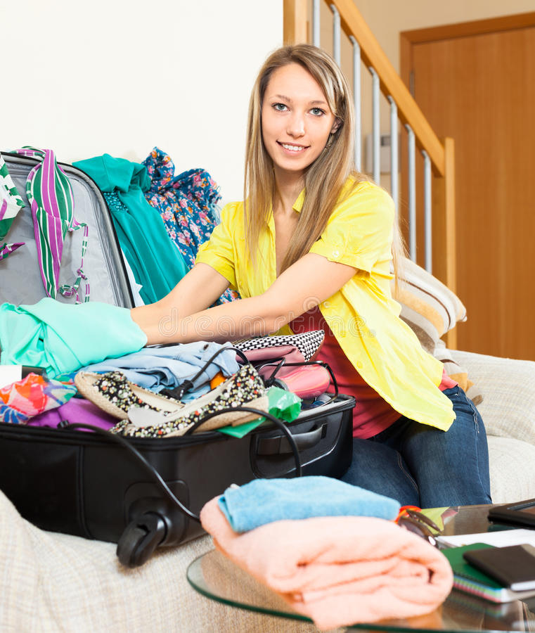 Smiling woman packs suitcase stock photo