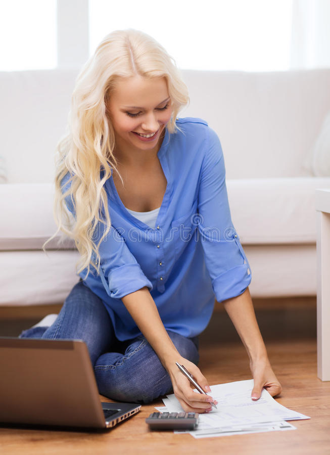 Smiling woman with papers, laptop and calculator. Tax, finances, technology, home and happiness concept - smiling young woman with papers, laptop computer and royalty free stock photography
