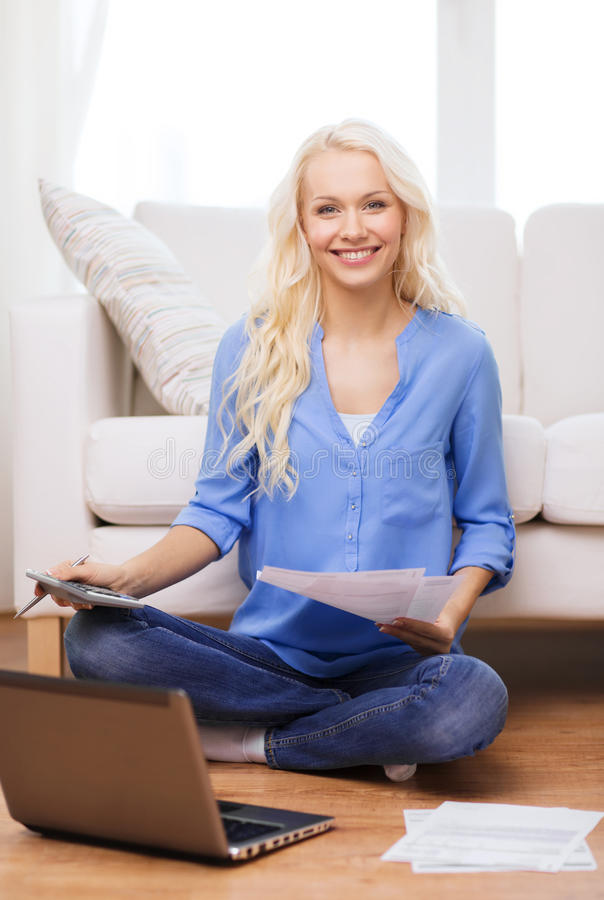 Smiling woman with papers, laptop and calculator. Tax, finances, technology, home and happiness concept - smiling young woman with papers, laptop computer and stock photo