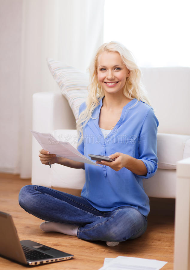 Smiling woman with papers, laptop and calculator. Tax, finances, technology, home and happiness concept - smiling young woman with papers, laptop computer and stock photography