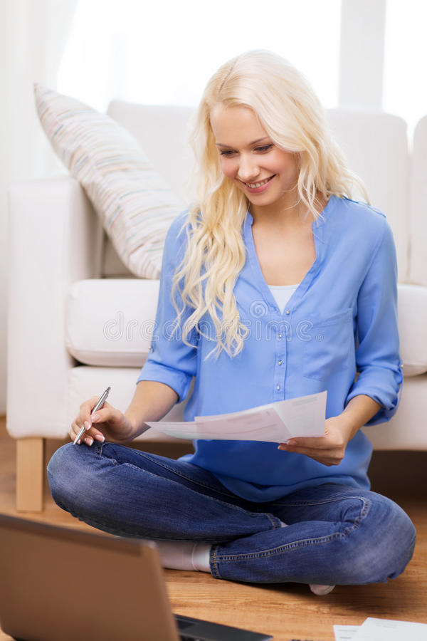 Smiling woman with papers, laptop and calculator. Tax, finances, technology, home and happiness concept - smiling young woman with papers and laptop computer at stock photos