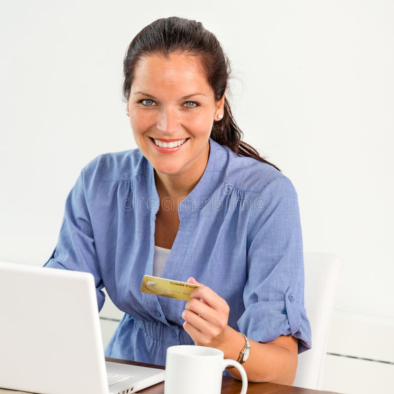 Smiling woman paying bills online banking home stock image