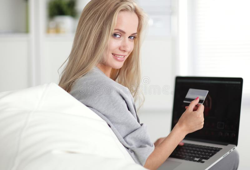 Smiling woman paying for online purchase with card stock image