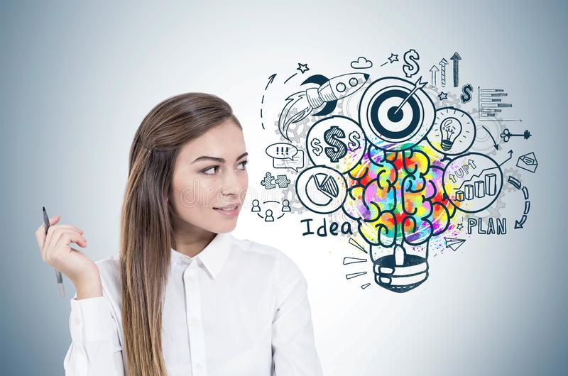 Smiling woman with pen, business idea. Portrait of smiling young businesswoman with long fair hair wearing white shirt, looking sideways and holding a pen stock photography