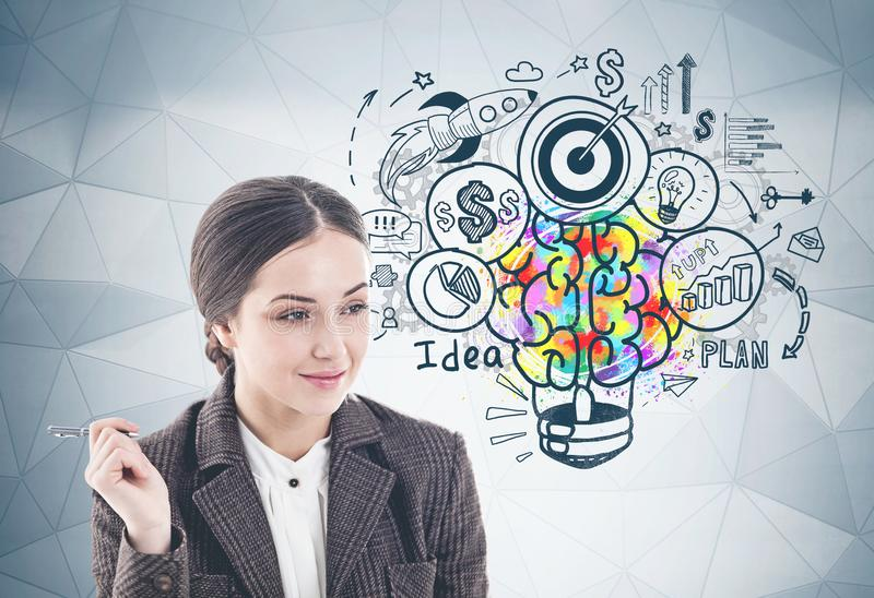 Smiling woman with pen and her business idea. Thoughtful young businesswoman with pen smiling standing near gray wall with colorful business idea sketch drawn on royalty free stock image