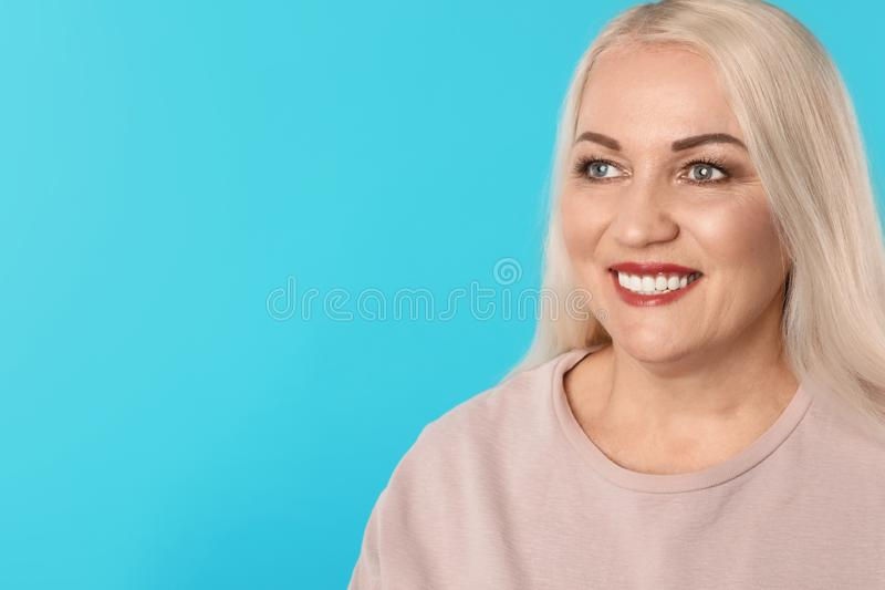 Smiling woman with perfect teeth on color background. Space for text stock images