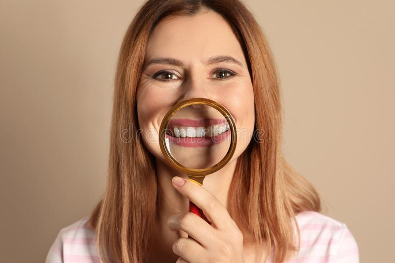 Smiling woman with perfect teeth and magnifier on color background. Closeup royalty free stock photography
